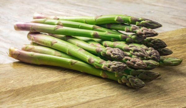 A bunch of freshly cut Mary Washington Asparagus laying on a wooden bench