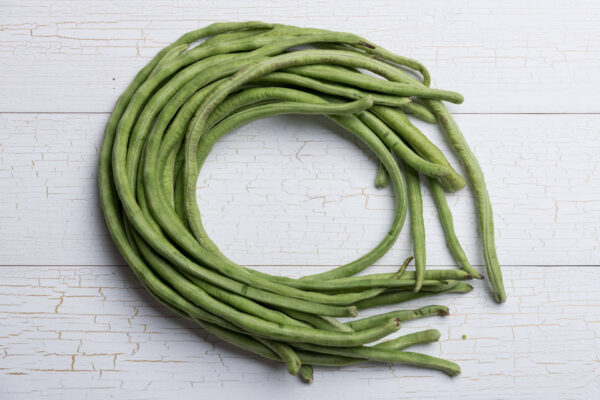 Snake Beans all curled up in a circle in a white wooden tabletop