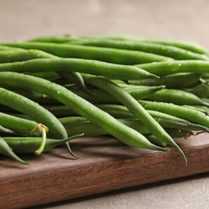 Fresh Windsor Long Pod beans on a awooden chopping board on a table