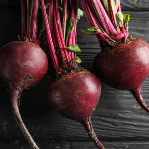 Three Detroit Dark Red Beetroots on a black table top