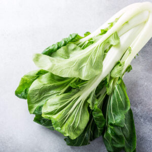 a freshly picked bok choi laying on a concrete table.