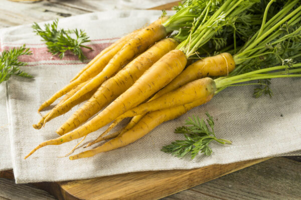 Half a dozen Solar Yellow Carrots on a cloth on a chopping board ready to be prepared