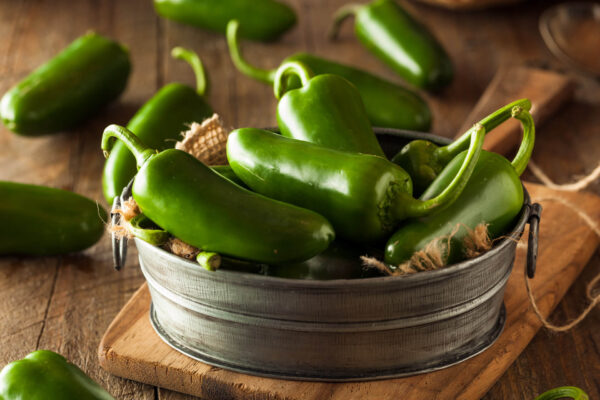 a metal bowl of jalapeno chilli on brown wooden table