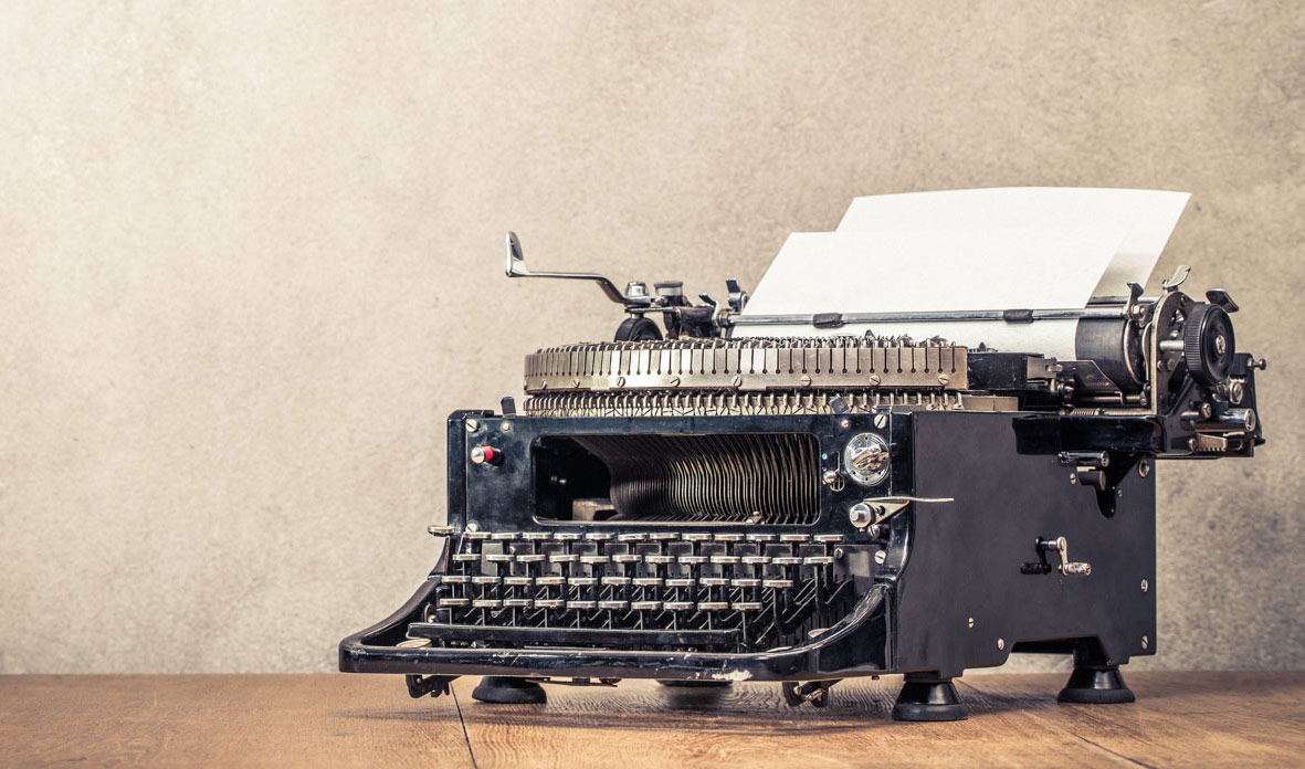 Old typewriter depicting contact us on white paper