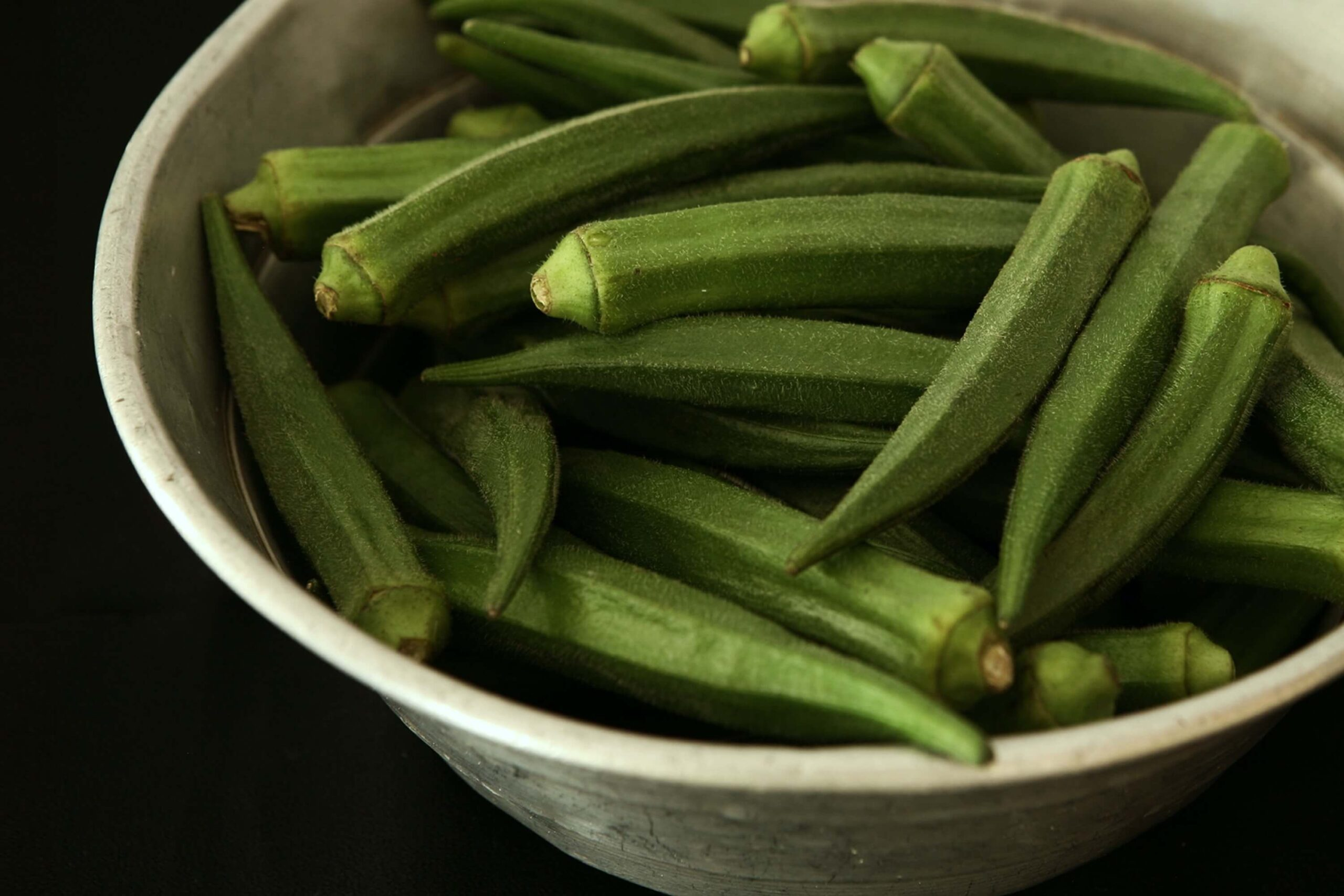 large white bowl of okra pods