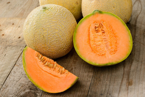 A sliced Hales Best rockmelon sitting on a table with a few uncut samples