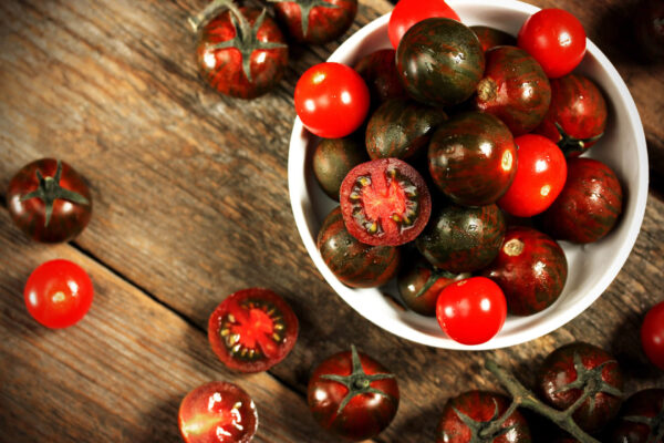 an abundance of Black Krim tomatoes in a white bowl on a wooden table