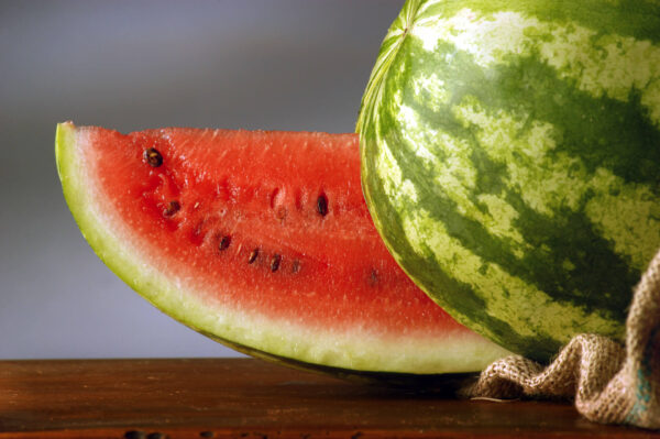 Large Slice of Bush Jubilee Watermelon next to the entire melon to show its red flesh