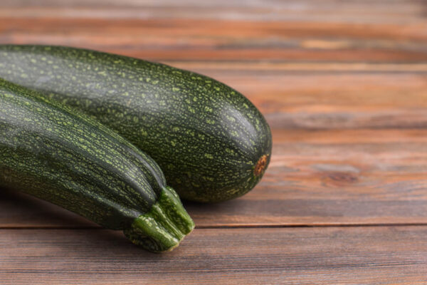 highlighting both ends of a black beauty zucchini that is sitting on a rustic wooden table