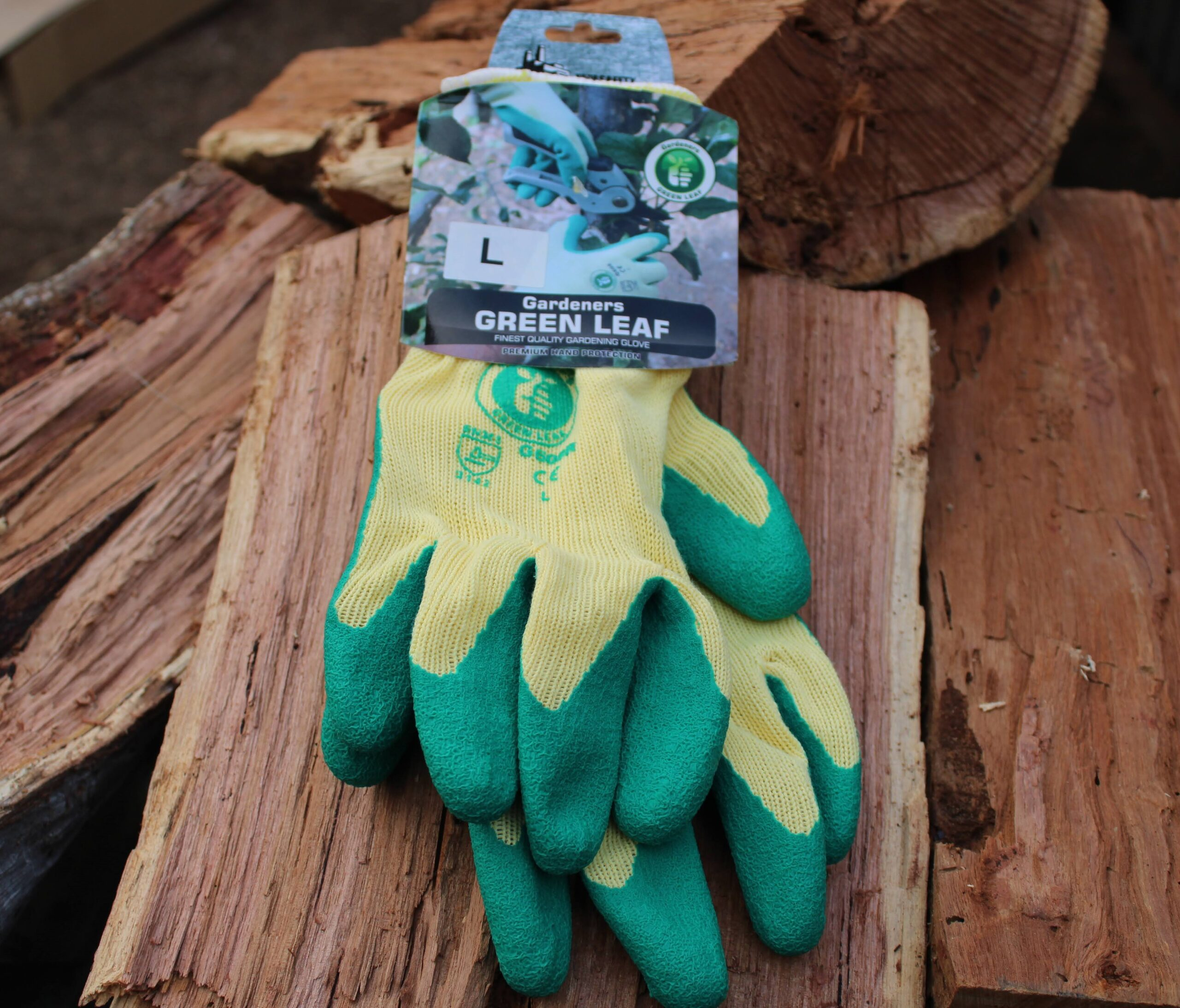 Green Leaf Gardening gloves on a wood stack