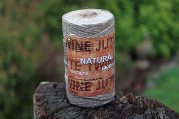 100m of Twine displayed on a log.