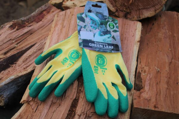 Green Gardening gloves on a wooden stack