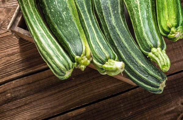 a bunch of cocozelle zucchini in a crate on a wood table