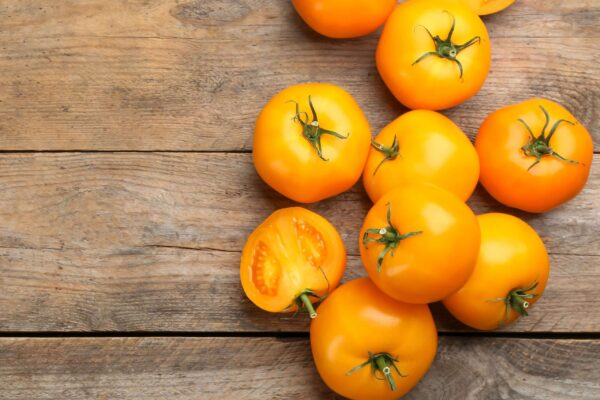 Yellow Grosse Lisse Tomatoes on a wooden board showing off its bright yellow colours